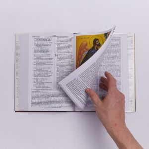 hand turning the page of bible