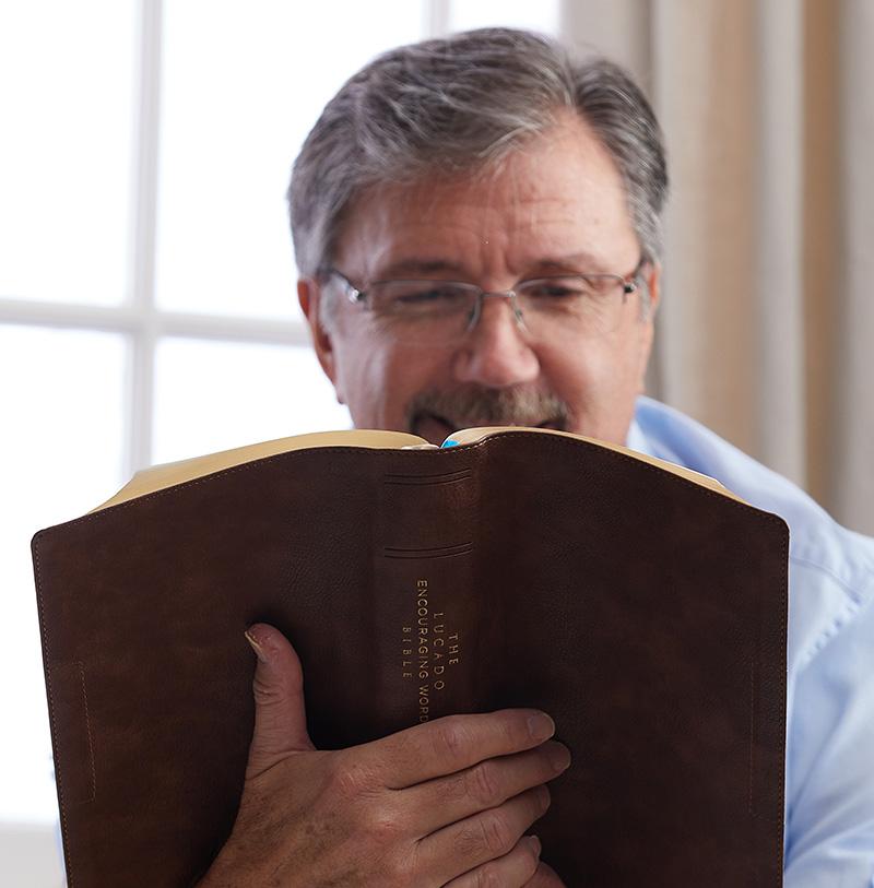 man reading Lucado Encouraging Word Bible